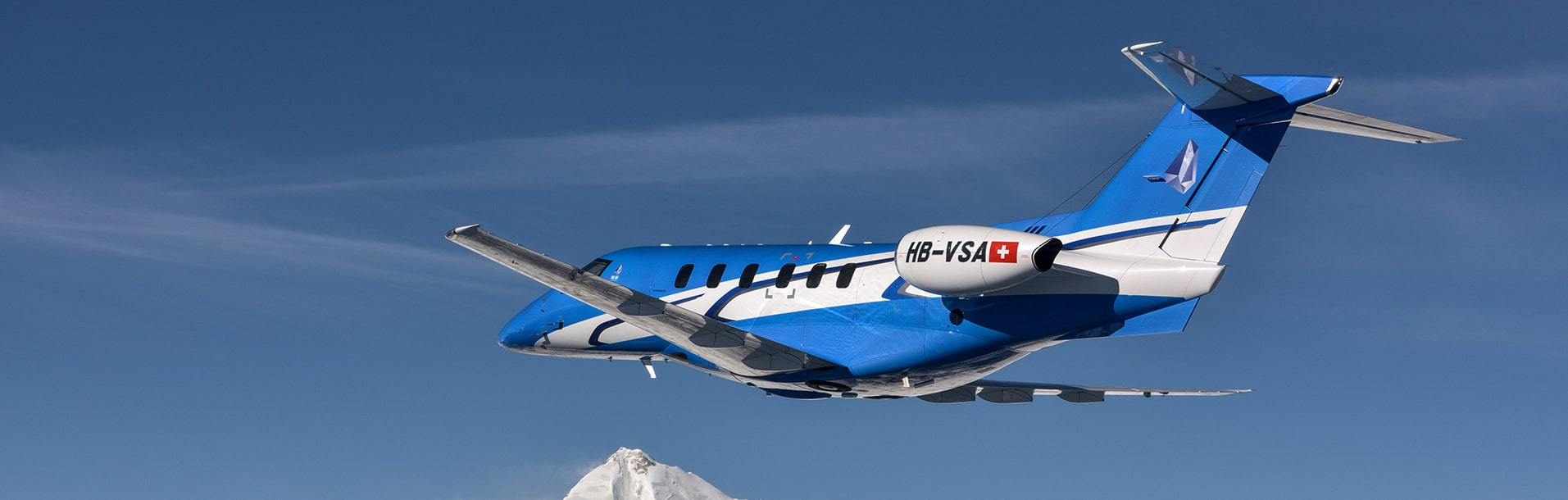 A pilatus PC-24 flying over moutains